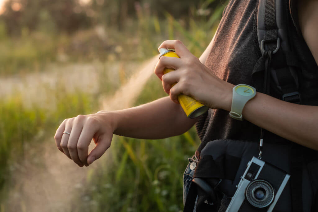 Woman using anti mosquito spray outdoors at hiking trip. Close-up of young female backpacker tourist applying bug spray on hands.